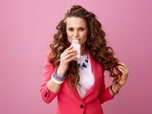 Mujer sonriente aislada en el yogur orgánico de consumición rosado de la granja Imágenes de archivo libres de regalías