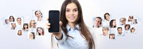 Mujer sonriente alegre que muestra la pantalla elegante en blanco del teléfono foto de archivo libre de regalías
