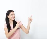 Mujer sonriente amistosa que señala en el copyspace aislado en el fondo blanco Foto de archivo libre de regalías