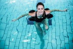 Mujer sonriente apta que hace aeróbicos de la aguamarina Imagen de archivo libre de regalías