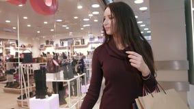Mujer sonriente apuesta en el centro comercial que mira mercancías metrajes