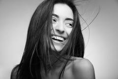 Mujer sonriente atractiva con el pelo largo en gris Fotos de archivo libres de regalías