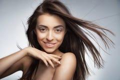 Mujer sonriente atractiva con el pelo largo en gris Fotografía de archivo