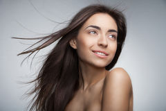 Mujer sonriente atractiva con el pelo largo en gris Imágenes de archivo libres de regalías
