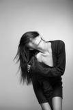 Mujer sonriente atractiva con el pelo largo en gris Fotografía de archivo libre de regalías