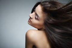 Mujer sonriente atractiva con el pelo largo en gris Foto de archivo libre de regalías