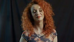 Mujer sonriente atractiva con el pelo rojo en un negro almacen de metraje de vídeo