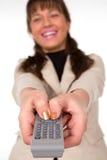 Mujer sonriente atractiva con el telecontrol de la TV Fotografía de archivo libre de regalías