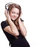 Mujer sonriente atractiva con los auriculares Imágenes de archivo libres de regalías