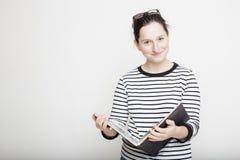 Mujer sonriente atractiva con los vidrios en su cabeza, colocándose con Fotografía de archivo