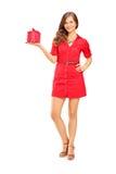 Mujer sonriente atractiva en el vestido que sostiene un regalo y que lo mira Foto de archivo libre de regalías