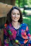 Mujer sonriente atractiva en fondo verde Imagen de archivo libre de regalías