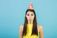 Mujer sonriente atractiva joven con el sombrero y el silbido del cumpleaños en fondo azul Celebración y partido Fotografía de archivo libre de regalías