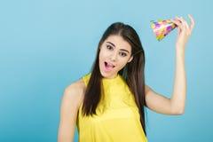 Mujer sonriente atractiva joven con el sombrero y el silbido del cumpleaños en fondo azul Celebración y partido Foto de archivo