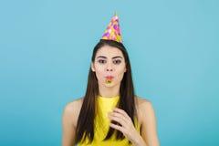 Mujer sonriente atractiva joven con el sombrero y el silbido del cumpleaños en fondo azul Celebración y partido Imagenes de archivo