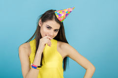 Mujer sonriente atractiva joven con el sombrero y el silbido del cumpleaños en fondo azul Celebración y partido Imagen de archivo