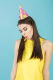 Mujer sonriente atractiva joven con el sombrero y el silbido del cumpleaños en fondo azul Celebración y partido Imágenes de archivo libres de regalías