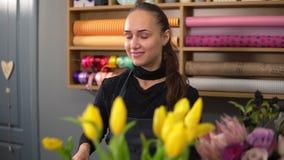 Mujer sonriente atractiva joven en el delantal que trabaja en tienda floral y que arregla el manojo de flor usando tulipanes amar metrajes