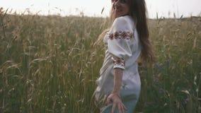 Mujer sonriente atractiva joven en el vestido blanco del étnico-estilo que corre juguetónamente lejos en el campo de cereal verde almacen de video