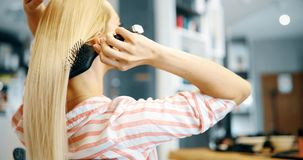 Mujer sonriente atractiva que cepilla su pelo Imagen de archivo