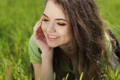 Mujer sonriente atractiva que descansa sobre la hierba verde, al aire libre portra Fotografía de archivo