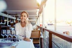 Mujer sonriente atractiva que habla en el teléfono de célula mientras que se sienta en café moderno de la acera en día caliente d Imagen de archivo libre de regalías