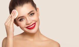 Mujer sonriente atractiva que usa el coj?n de algod?n imagenes de archivo