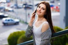 Mujer sonriente bastante elegante de los jóvenes que habla en el teléfono elegante en Fotografía de archivo