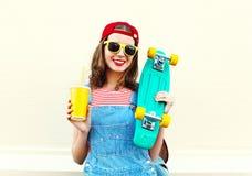 Mujer sonriente bastante fresca feliz con la taza y el monopatín sobre blanco Imagen de archivo