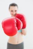 Mujer sonriente Blurred en guantes de boxeo rojos Foto de archivo libre de regalías