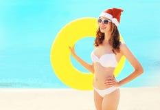 Mujer sonriente bonita de la Navidad en el sombrero rojo de santa con el círculo inflable en la playa sobre el mar azul Foto de archivo
