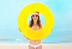 Mujer sonriente bonita del retrato de la Navidad en el sombrero rojo de santa con el círculo inflable en la playa sobre el mar Foto de archivo libre de regalías