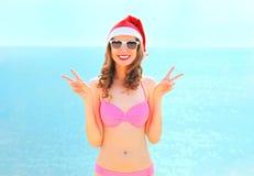 Mujer sonriente bonita del retrato de la Navidad en el sombrero rojo de santa en la playa sobre fondo del mar Imagenes de archivo