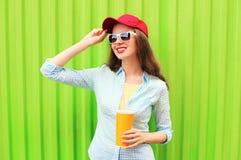 Mujer sonriente bonita en gafas de sol con la taza de zumo de fruta sobre verde colorido Fotografía de archivo