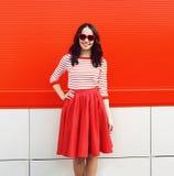 Mujer sonriente bonita en gafas de sol y vestido rojos Imagenes de archivo