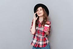 Mujer sonriente bonita en sombrero que habla en el teléfono móvil Imagen de archivo libre de regalías