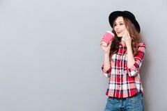 Mujer sonriente bonita en sombrero que habla en el teléfono móvil Imágenes de archivo libres de regalías