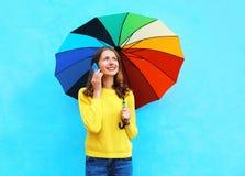 Mujer sonriente bonita feliz con el paraguas colorido que habla en smartphone en día del otoño sobre fondo azul colorido Imágenes de archivo libres de regalías