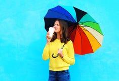 Mujer sonriente bonita feliz con la taza de café y el paraguas colorido en el día del otoño que mira para arriba sobre fondo azul Imagen de archivo