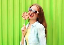 Mujer sonriente bonita feliz del retrato con la piruleta sobre verde colorido Fotos de archivo libres de regalías