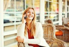 Mujer sonriente bonita feliz que habla en smartphone en el café Fotografía de archivo