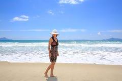 Mujer sonriente bonita joven que da un paseo a lo largo de Sandy Beach Imágenes de archivo libres de regalías