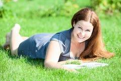 Mujer sonriente bonita que miente en hierba verde con el libro Imágenes de archivo libres de regalías