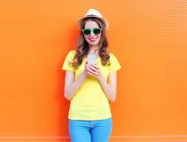 Mujer sonriente bonita que usa smartphone sobre naranja colorida Fotografía de archivo