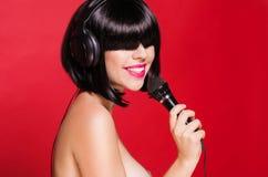 Mujer sonriente cantante hermosa con el micrófono Fotos de archivo