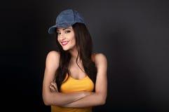 Mujer sonriente casual hermosa en gorra de béisbol azul y t amarillo Fotografía de archivo