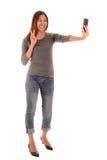 Mujer sonriente casual que hace la foto del selfie por smartphone en blanco Fotos de archivo libres de regalías
