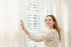 Mujer sonriente cerca de la ventana fotografía de archivo libre de regalías
