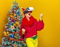 Mujer sonriente cerca del árbol de navidad con los vidrios de VR que disfruta Imagenes de archivo