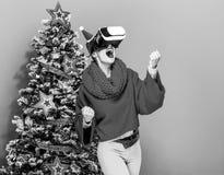 Mujer sonriente cerca del árbol de navidad con los vidrios de VR que disfruta Imagen de archivo